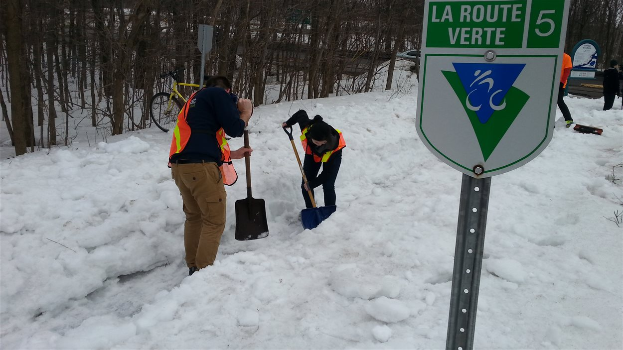 Des citoyens déneigent une piste cyclable près de l'entrée nord du pont de Québec.