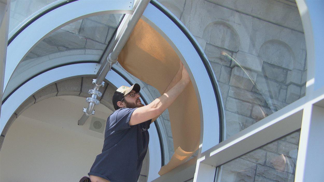 Un employé de la Ville d'Ottawa installe des feuilles de papier sur la passerelle vitrée.