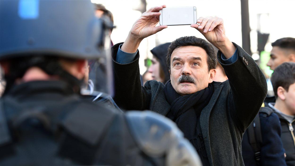 Le journaliste et fondateur de Médiapart, Edwy Plenel, prend des photos lors d'une manifestation d'étudiants s'opposant à la Loi Travail à Paris, le 17 mars 2016