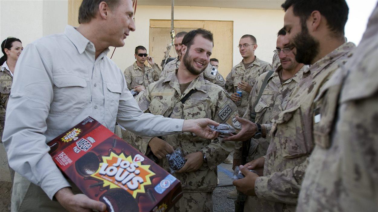 Le ministre des Affaires étrangères, Maxime Bernier, offre des Jos. Louis aux soldats canadiens à la base de patrouille Wilson, dans le district de Zhari, en Afghanistan, le 7 octobre 2007.