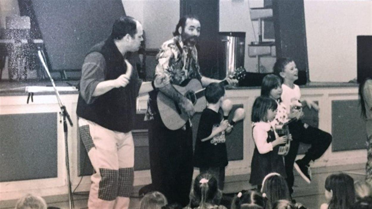 Raffi chante pour les élèves.