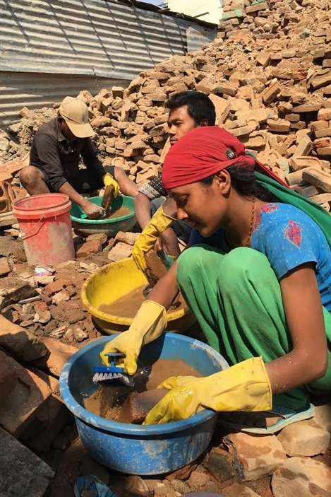 Un an après le séisme, l'opération nettoyage n'est toujours pas terminée dans le pays. Cette famille dégage les briques de décombres et les nettoie dans l'espoir de les réutiliser un jour.