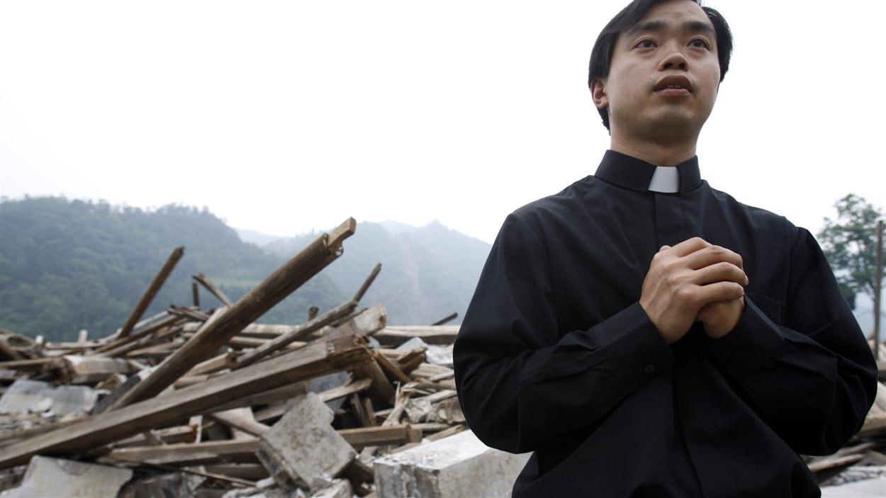 Un prêtre catholique devant une église du canton de Bailu détruite par un séisme en mai 2008