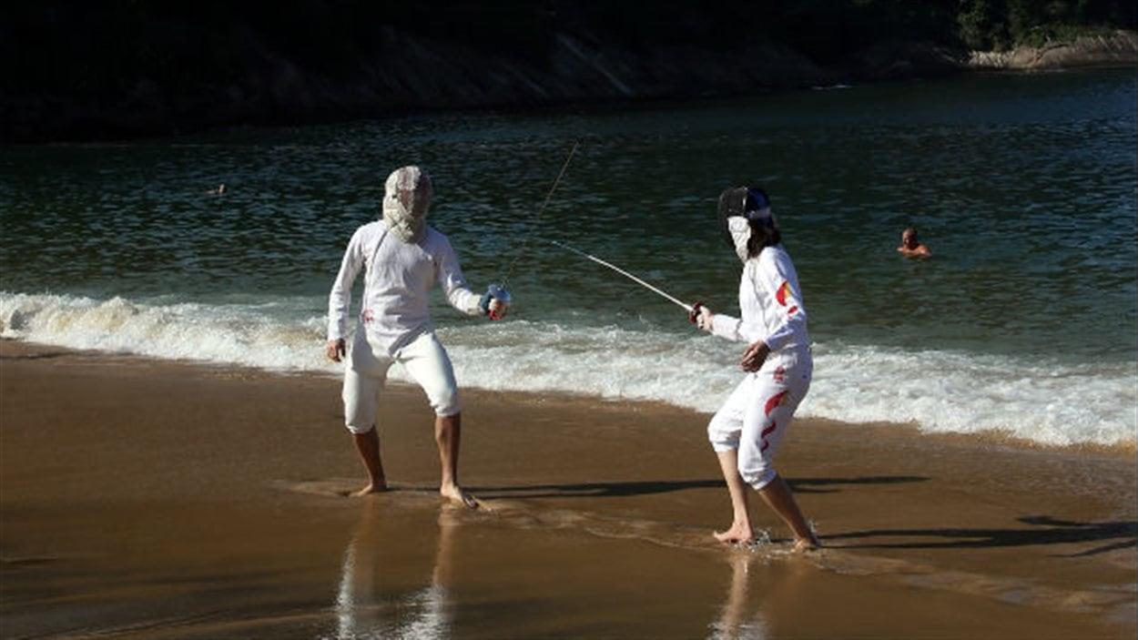 En marge des Championnats du monde par équipe d'escrime, qui se déroulaient en début de semaine à Rio de Janeiro, l'escrimeur canadien Joseph Polossifakis et la Chinoise Lu Huilin mettent leur jeu de pied à l'épreuve sur la plage près du « Pain de sucre ».