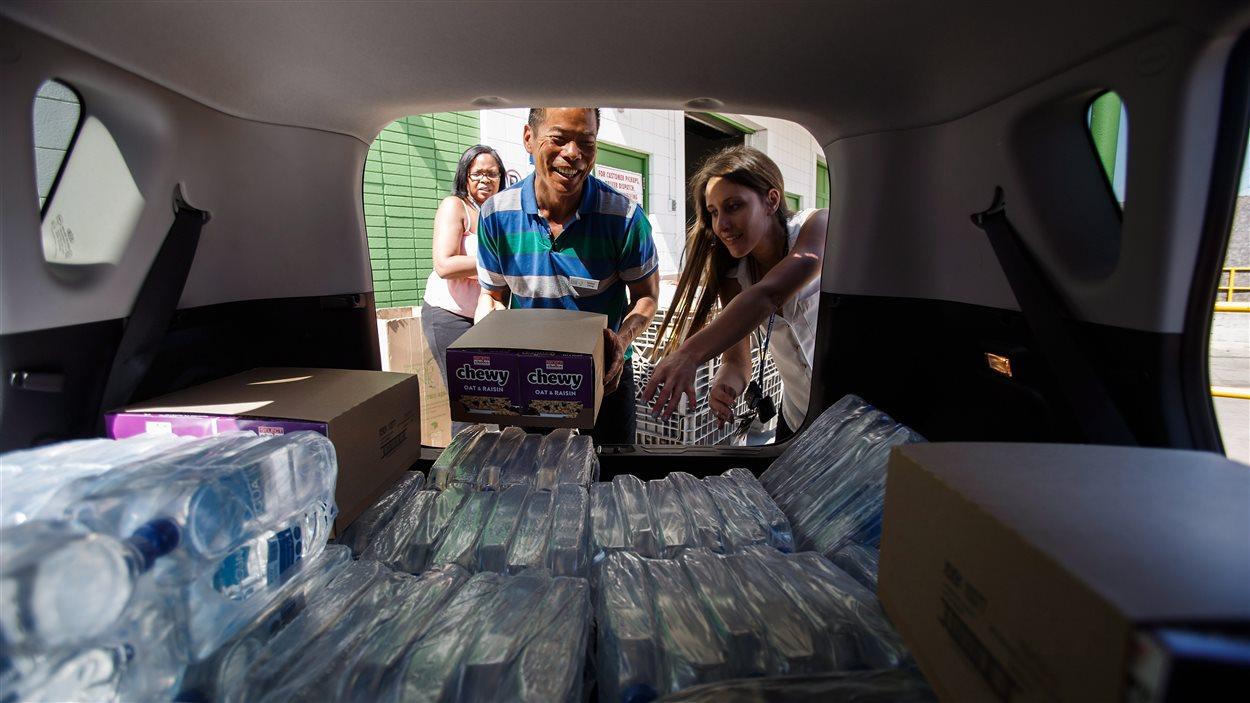 Des travailleurs sociaux remplissent de  denrées un véhicule de la banque alimentaire d'Edmonton pour aider les évacués de Fort McMurray.