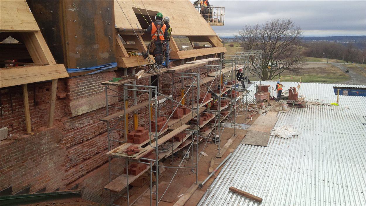 Réfection d'un façade de briques au-dessus de la future salle multifonctionnelle.