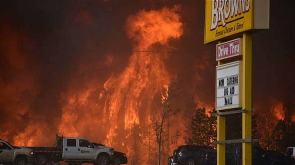 Un rideau de flammes en arrière plan avec des voitures et l'affiche d'une entreprise en avant plan.