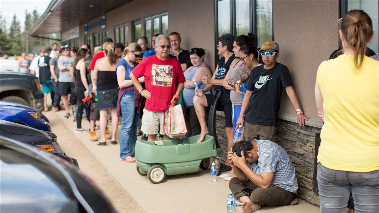 Des résidents de Fort McMurray font la file devant un supermarché d'Anzac, en Alberta. L'évacuation de Fort McMurray a été ordonnée après que des feux de forêt se sont déclarés dans la région.