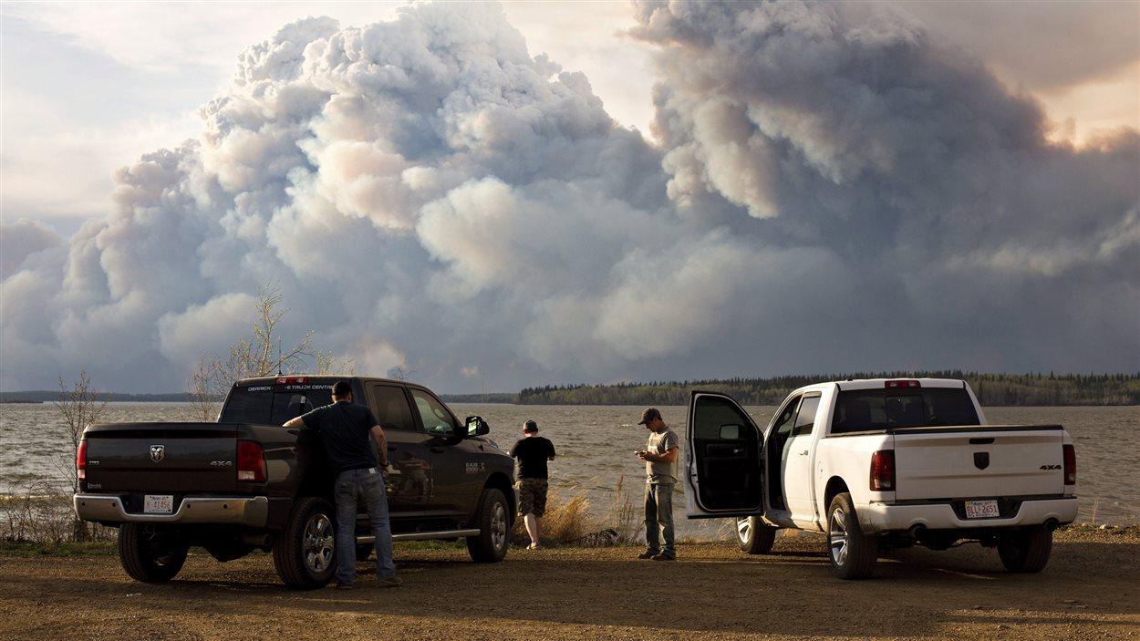 Des évacués observent à distance le feu de Fort McMurray.
