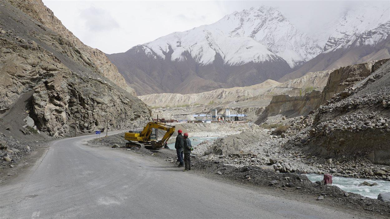 Des travailleurs regardent une route en construction en Chine.