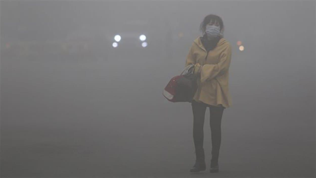 Une femme portant un masque se tient debout au milieu d'un épais smog dans la ville chinoise de Harbin.
