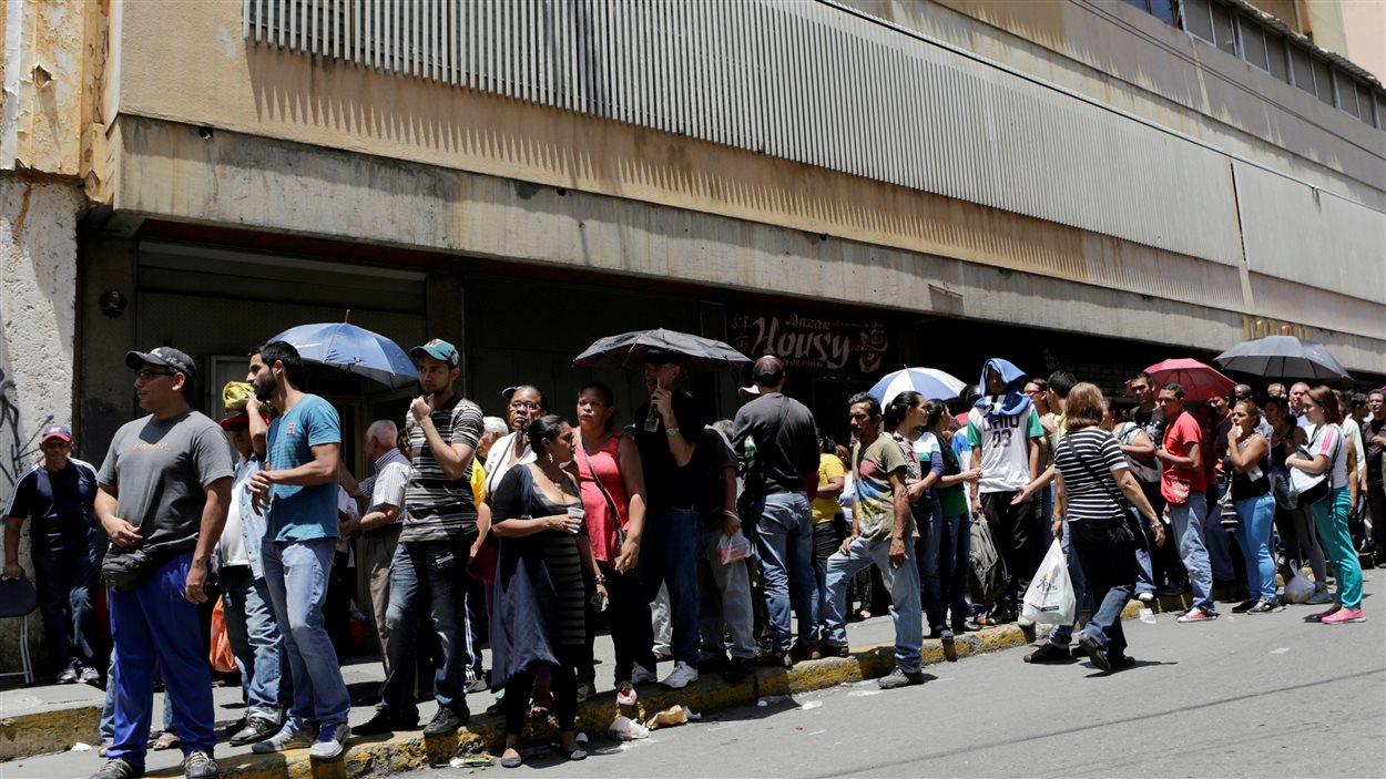 Des personnes font la queue devant un supermarché pour acheter des produits de base, à Caracas, au Venezuela.