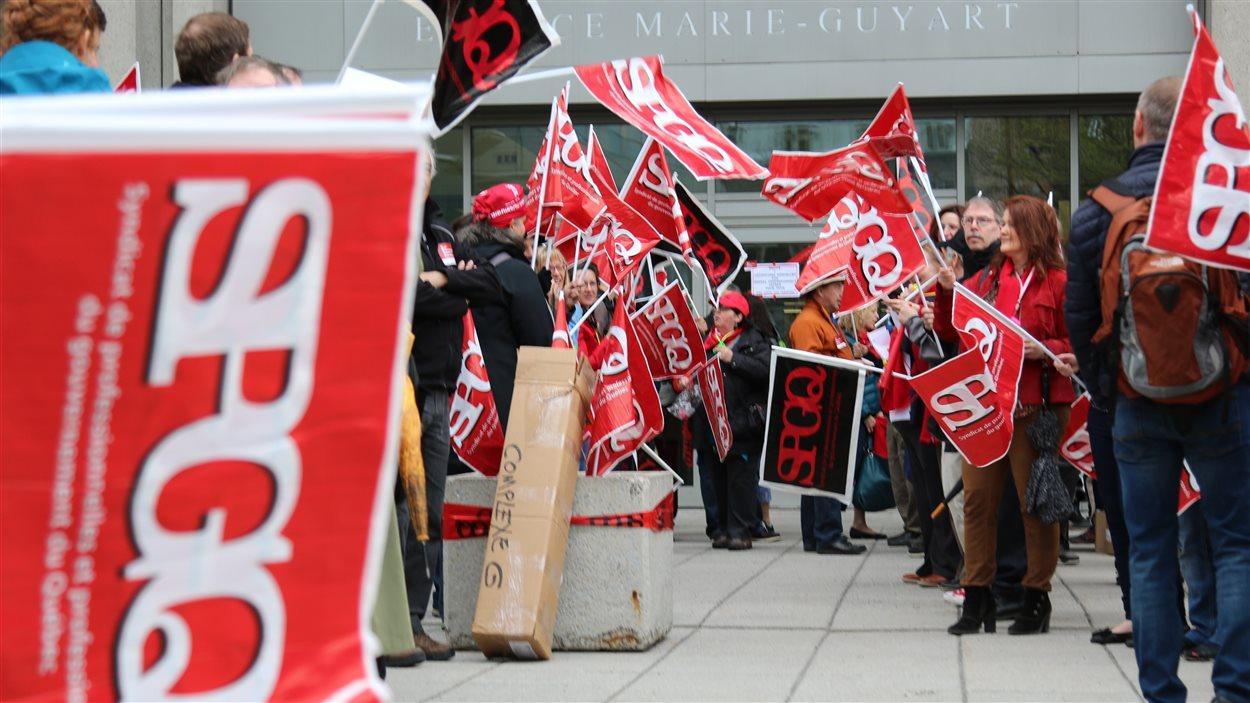 Des professionnels manifestent devant l'édifice Marie-Guyart à Québec.