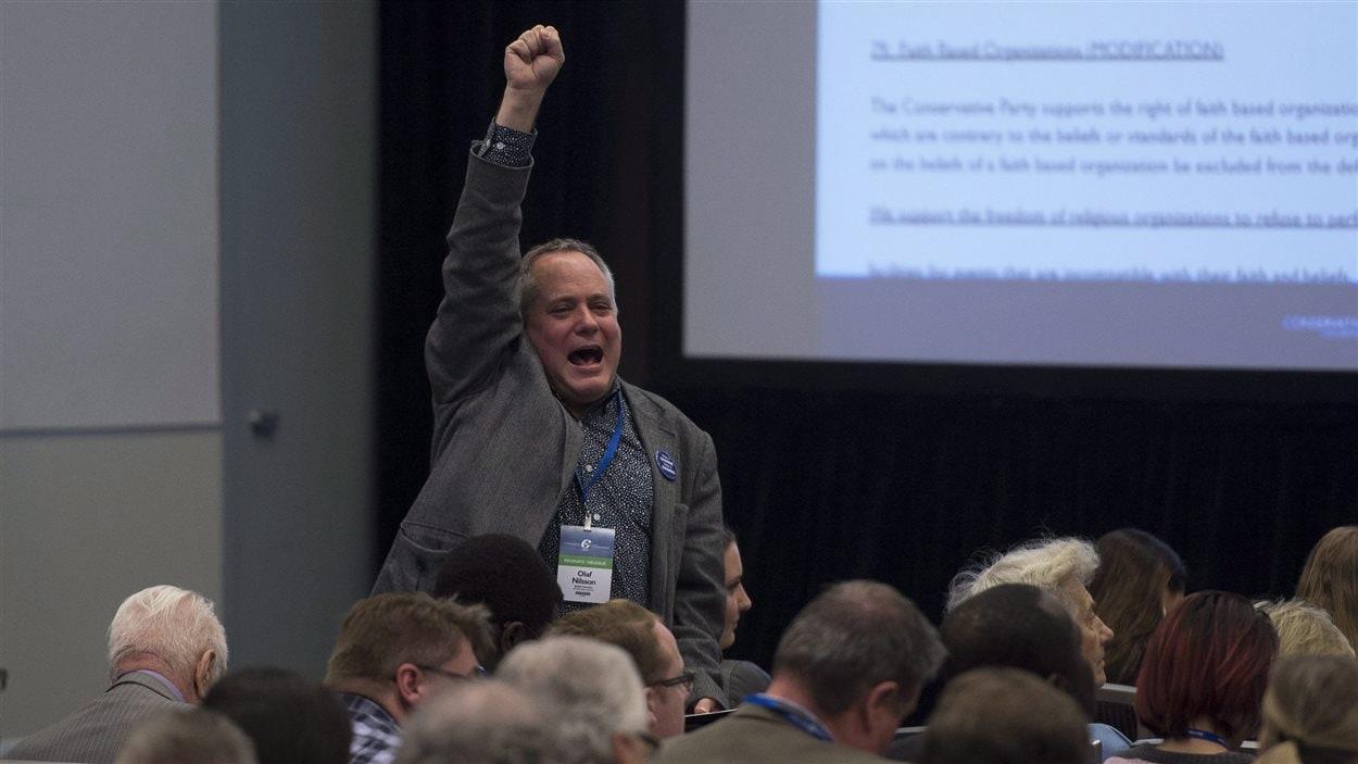 Un délégué conservateur célèbre après avoir gagné un vote préliminaire pour modifier la politique du parti sur le mariage gai.