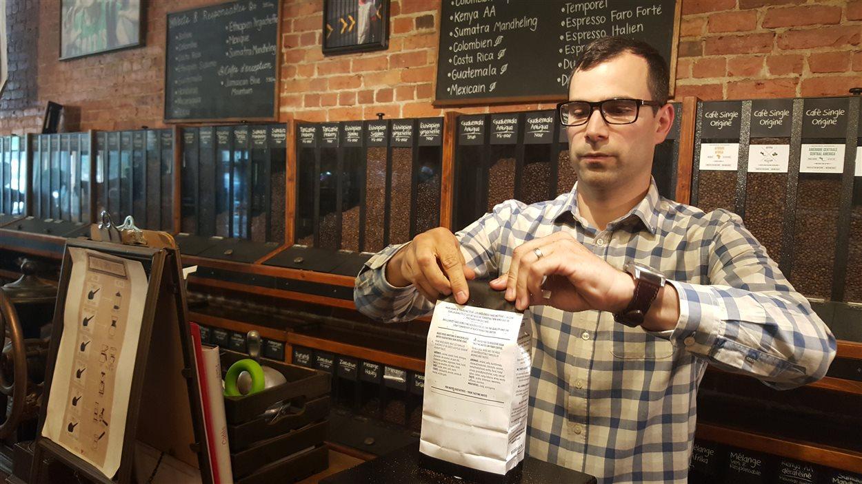 Maxime Fabi, copropriétaire des Brûleries Faro, en train de fermer un sac de café.