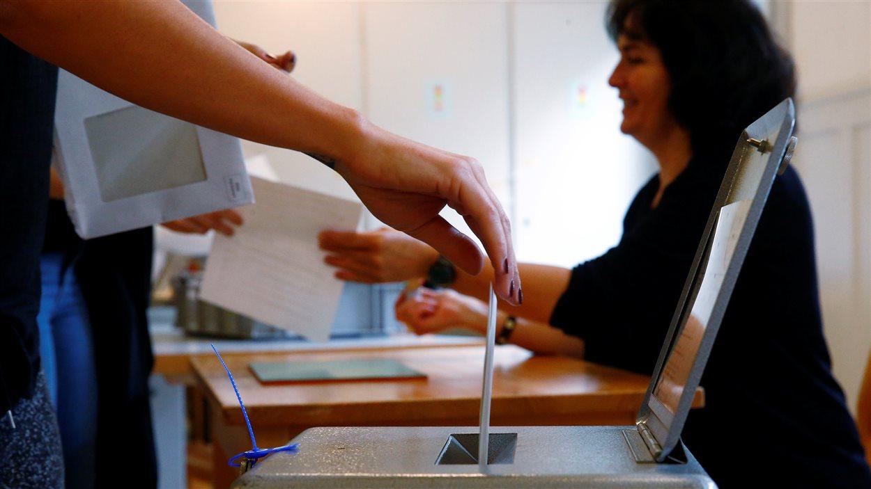 Des électeurs déposent leurs bulletins de vote dans une école de Bern, en Suisse, durant une consultation sur l'idée d'un revenu de base inconditionnel, le 5 juin 2016.