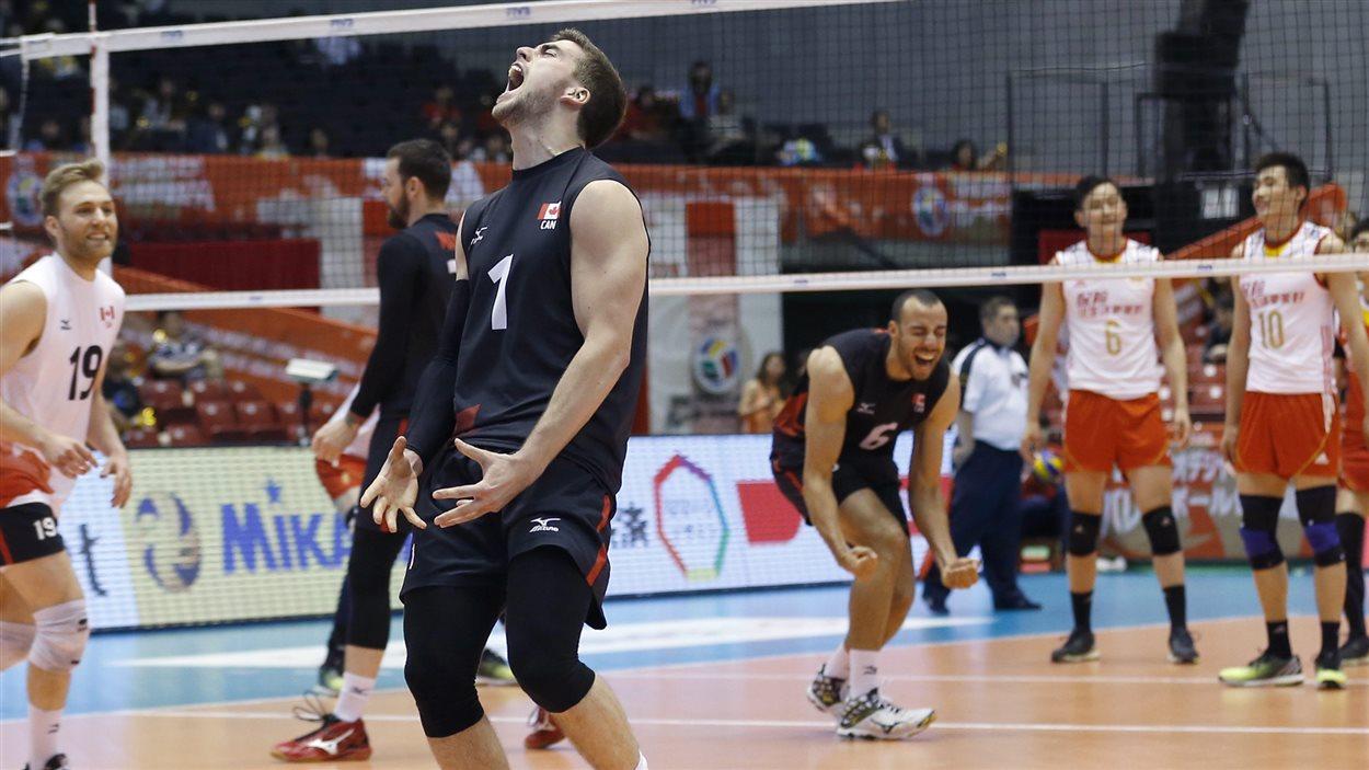 Les joueurs de l'équipe canadienne de volleyball, dont Tyler Sanders (no 1) célèbrent au Japon.