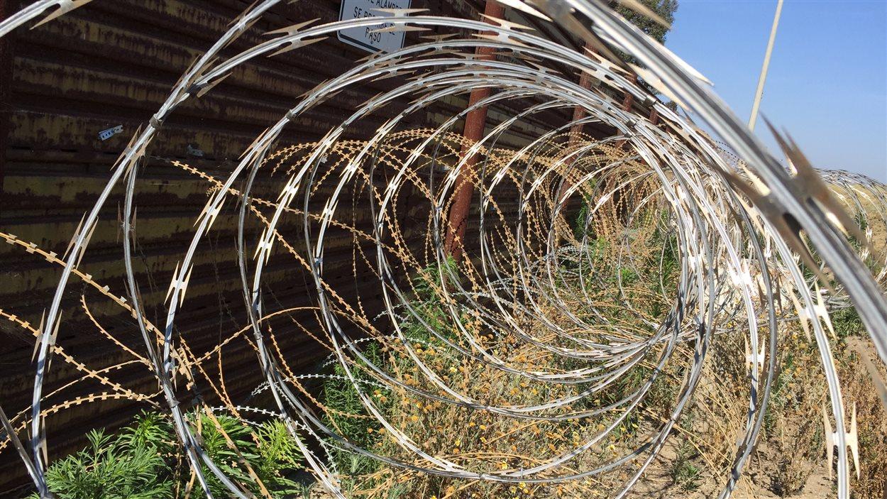 Des barbelés pour empêcher les gens de traverser le mur entre les États-Unis et le Mexique.