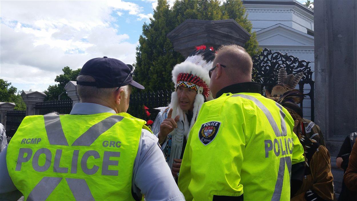 Le grand chef Carle s'explique avec deux agents de police à son arrivée devant Rideau Hall.