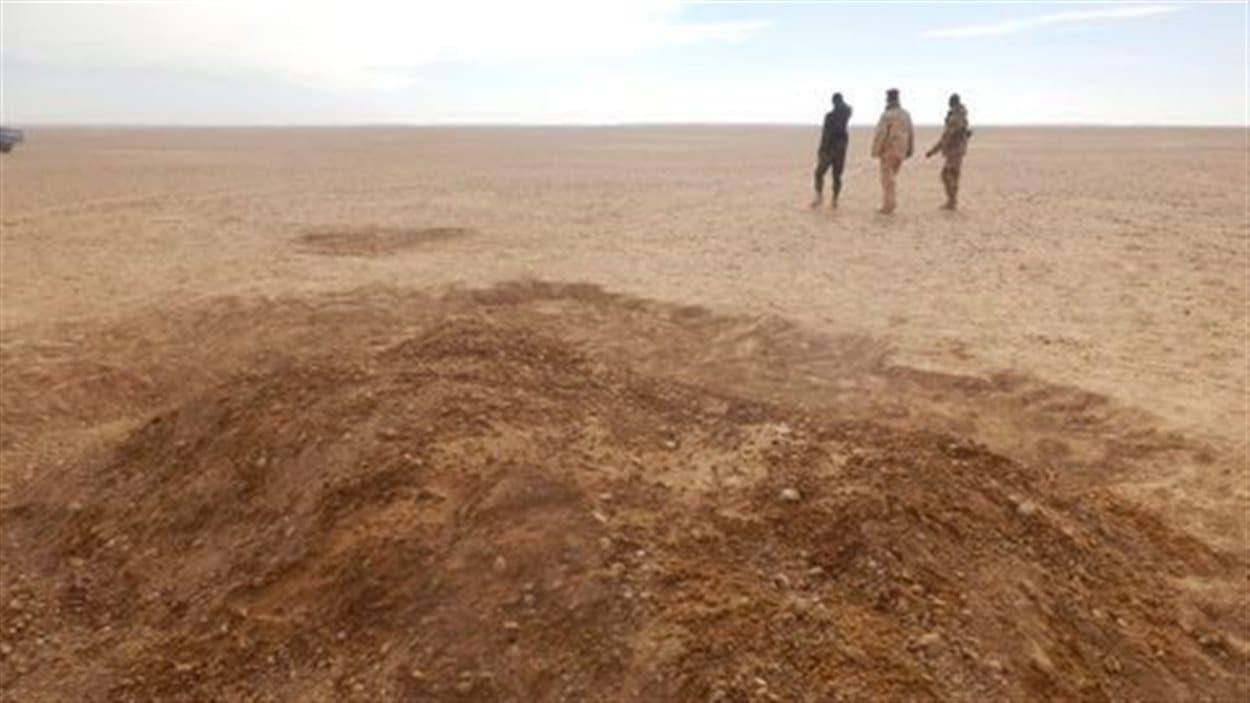 Dans le désert du Niger, la tombe fraîchement creusée de migrants morts de soif en tentant de rejoindre l'Algérie en 2013.