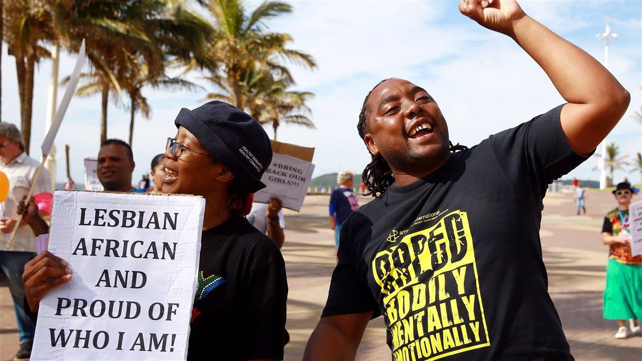 Deux militants pour les droits des homosexuels manifestent, dont une qui tient une pancarte qui dit : «Africaine lesbienne et fière de qui je suis!»