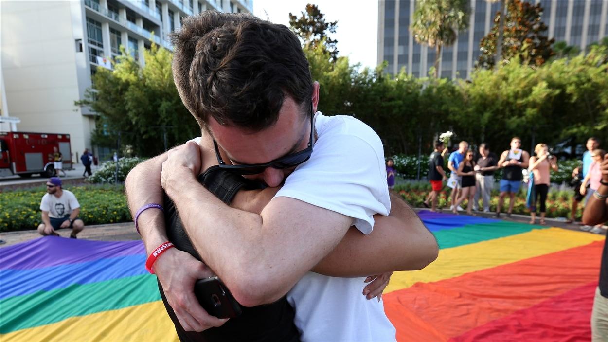 Deux hommes s'enlacent lors d'un rassemblement à Orlando en mémoire des victimes de la tuerie du club gai Pulse.