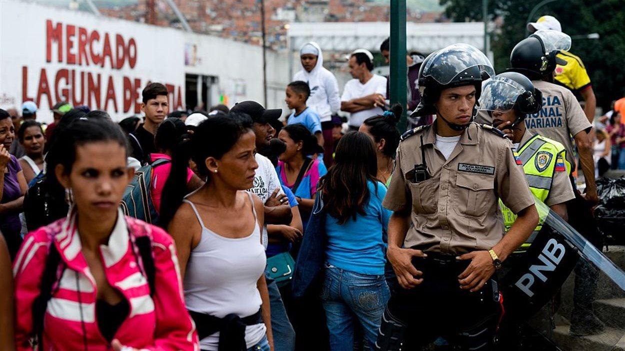 La police surveille les citoyens qui font la file pour acheter l'épicerie à Caracas, au Venezuela, le 11 juin 2016.