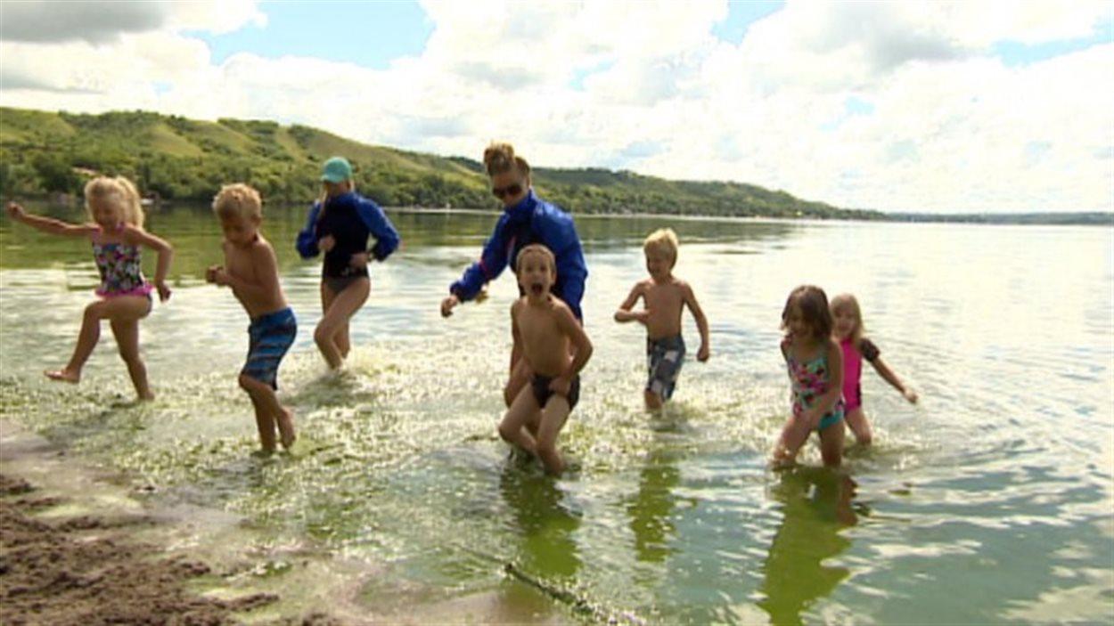 Des enfants se baignent dans un lac.