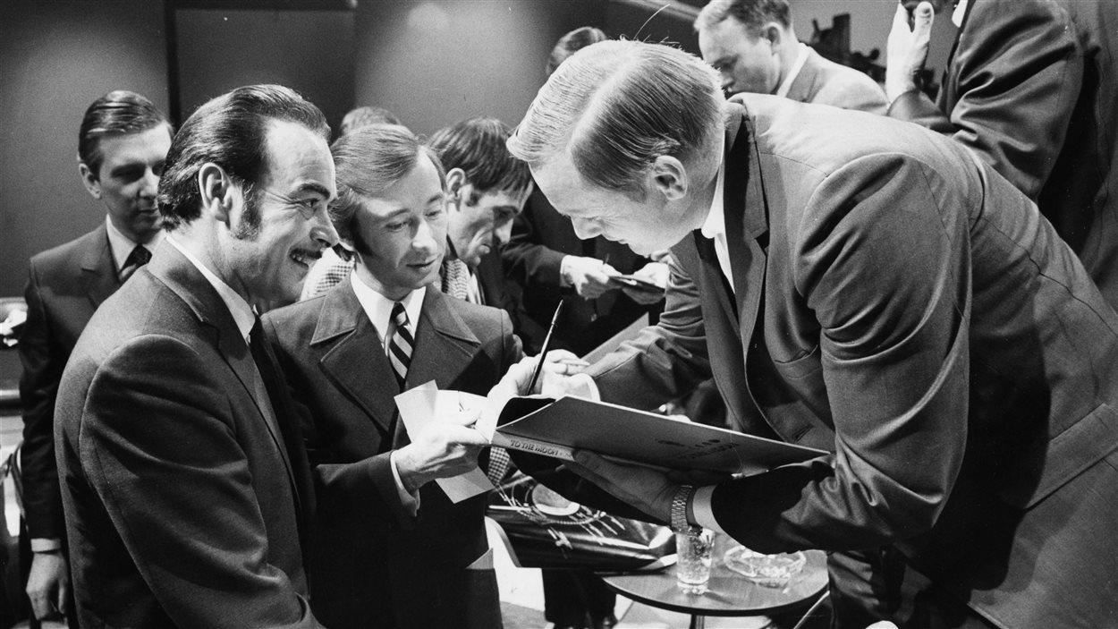 L'animateur et journaliste Henri Bergeron et Claude Jean Devirieux lors d'une conférence de presse des astronautes d'Apollo XI. Neil A. Armstrong dédicace un album. En arrière-plan, les astronautes Michael Collins et Edwin E. Aldrin.