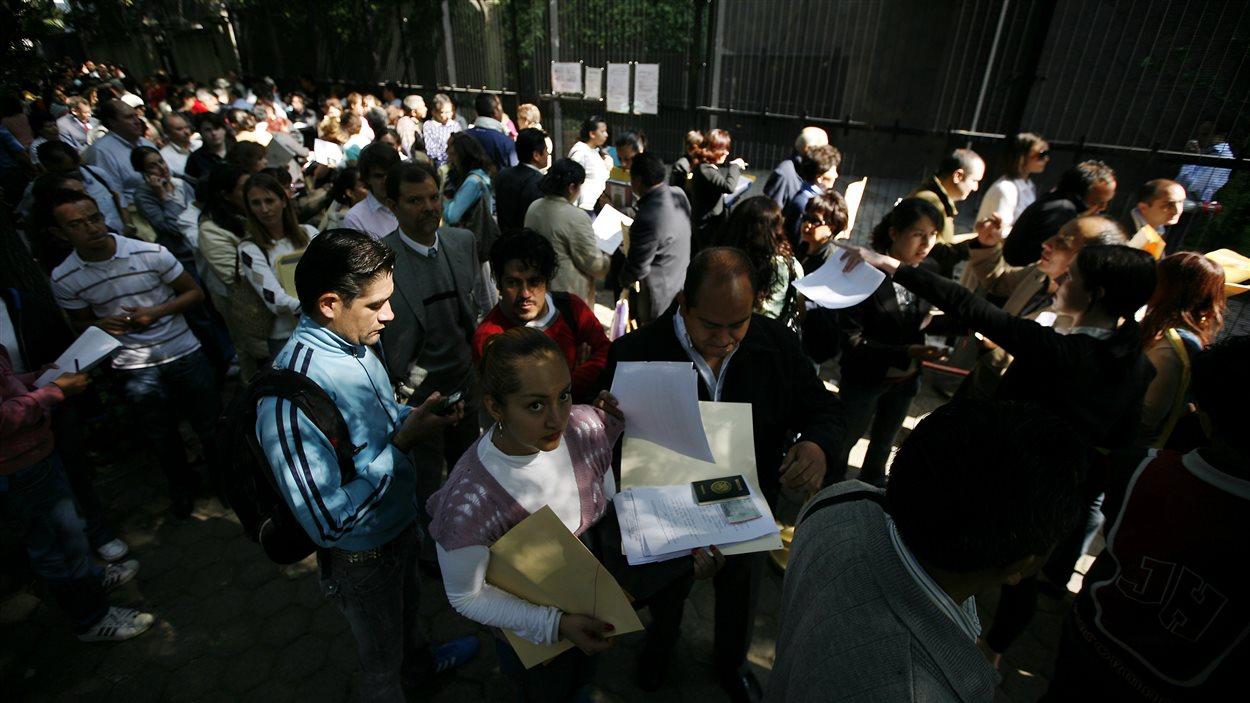 Des Mexicains attendent devant l'ambassade du Canada à Mexico, quelques jours après que le gouvernement canadien ait décidé d'imposer un visa, en 2009.