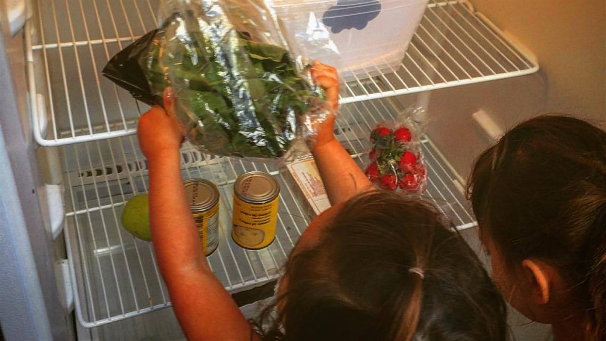 Deux jeunes filles déposent des denrées dans le frigo communautaire de sherbrooke