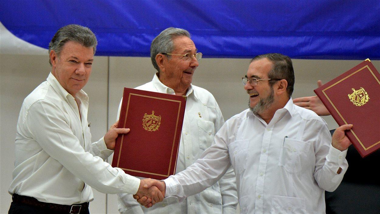 Le président colombien Juan Manuel Santos et le chef des FARC Rodrigo Londono se sont serré la main sous le regard du président cubain Raul Castro.
