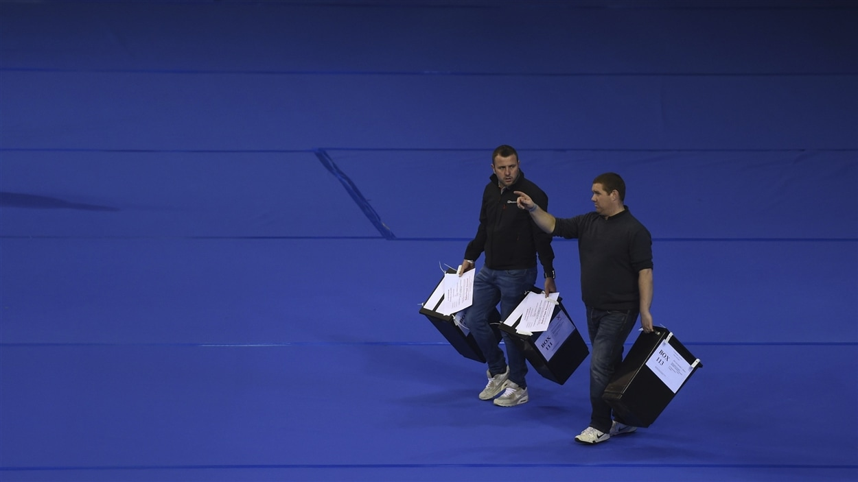 À la fermeture des bureaux de vote, deux hommes transportent des urnes pour dépouillement, à Glasgow, en Écosse.
