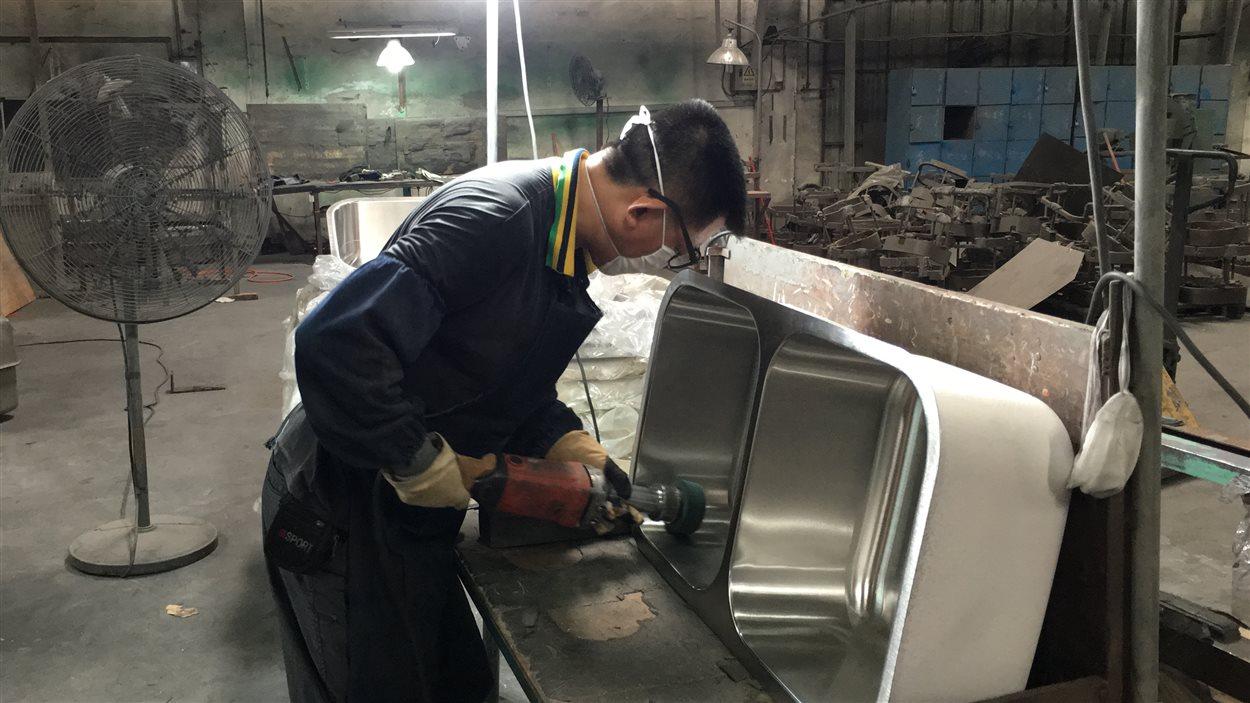 Un ouvrier chinois travaillant dans une usine d'éviers de Foshan.