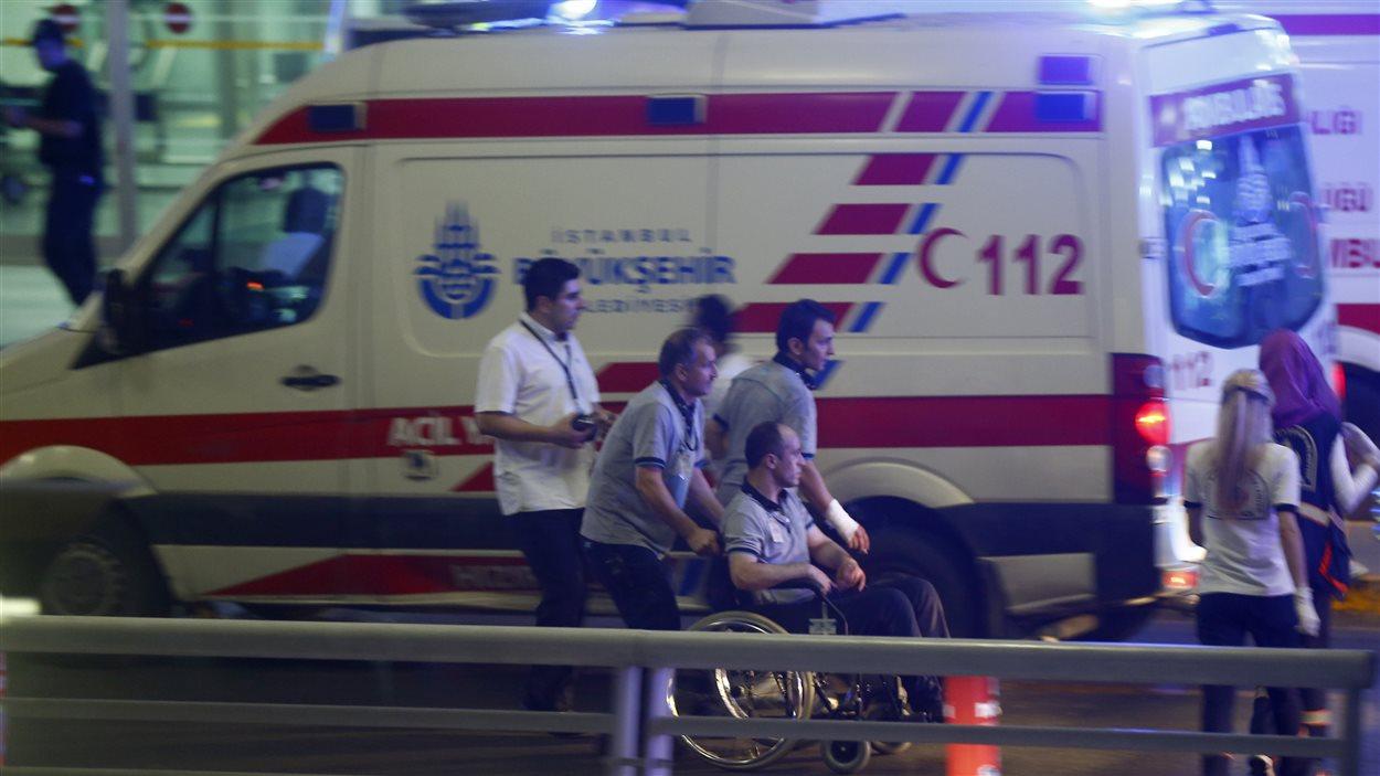 Des ambulanciers viennent en aide à un homme blessé dans les explosions à l'aéroport d'Istanbul en Turquie.