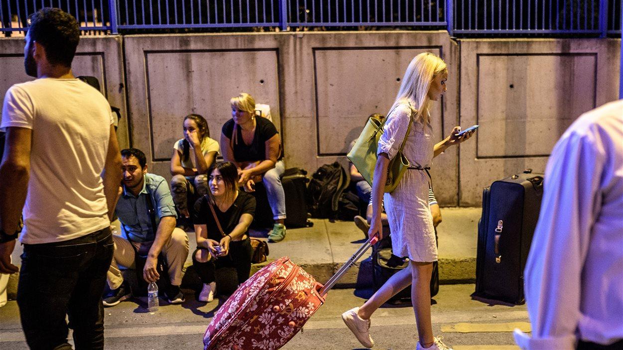 Plusieurs personnes attendent à l'extérieur de l'aéroport d'Istanbul avec leurs bagages après les explosions.