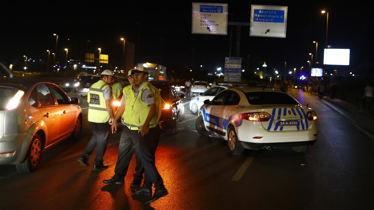 Des policiers s'occupent de la circulation à proximité de l'aéroport d'Istanbul où deux explosions ont eu lieu.