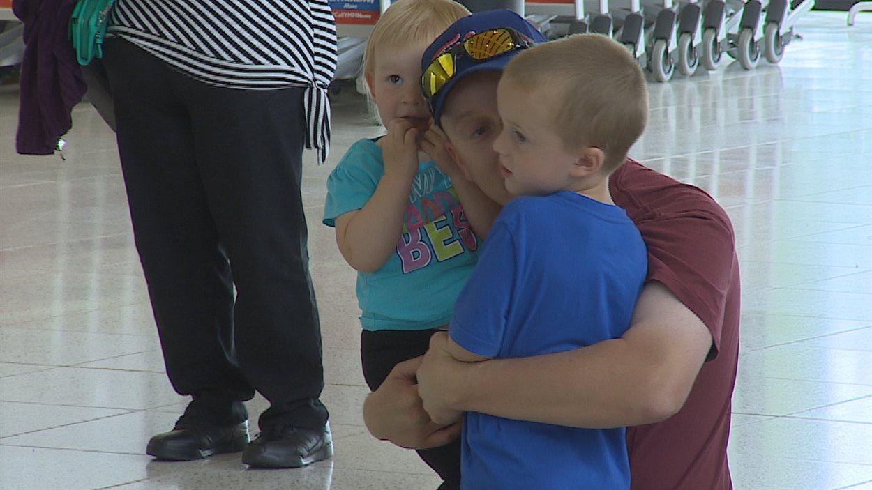Les retrouvailles de père et ses enfants à l'aéroport de Fort McMurray.