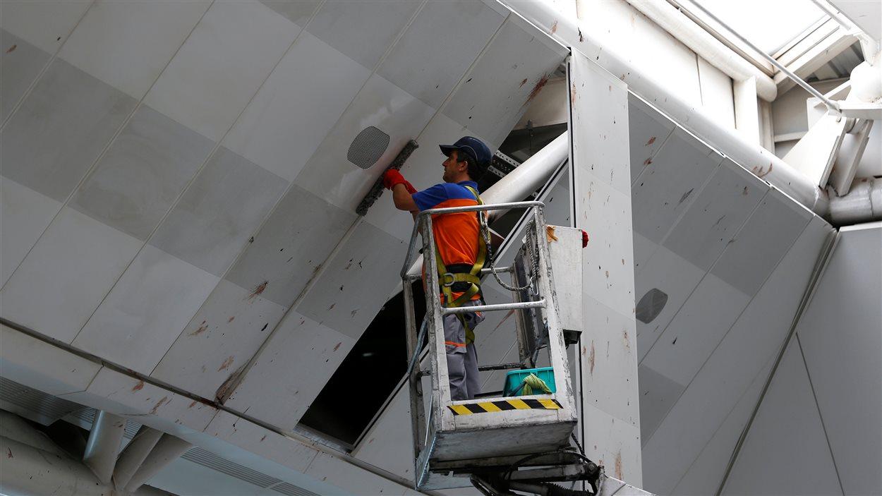 Un employé nettoie le toit du terminal des départs internationaux à l'aéroport d'Istanbul après les explosions.