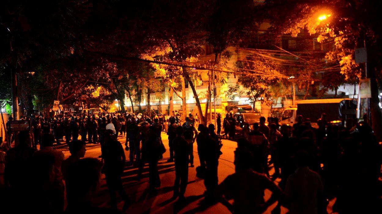 Des dizaines de gardes de sécurité encerclent le restaurant où une vingtaine de personnes sont prises en otage à Dacca, au Bangladesh.