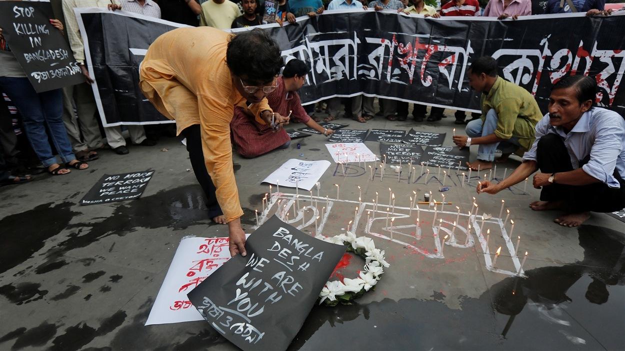 Un homme place une affiche à la mémoire des victimes du Bangladesh; en Inde, comme ailleurs en Asie, l'attaque de l'EI dans un café de Dacca a suscité un mouvement de solidarité.