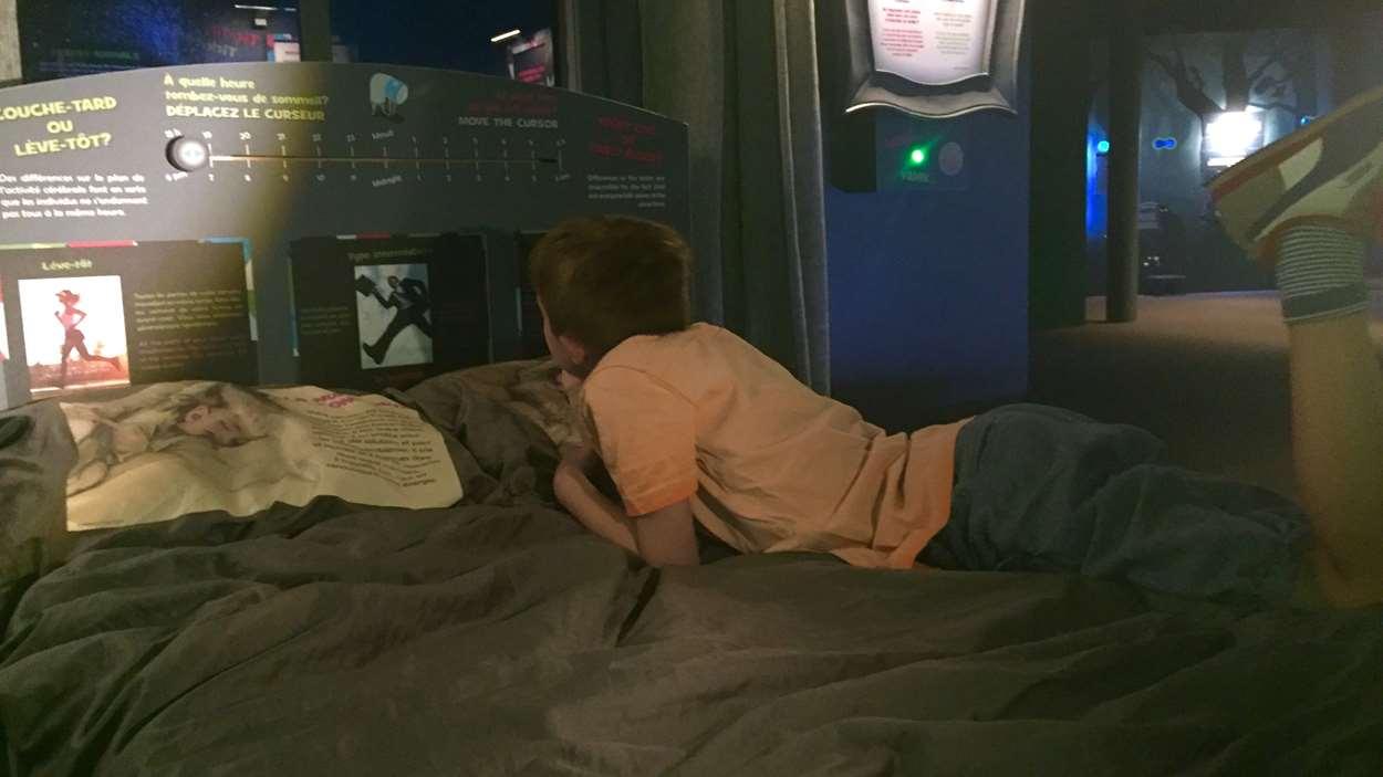 Un enfant allongé sur un lit qui regarde des tableaux