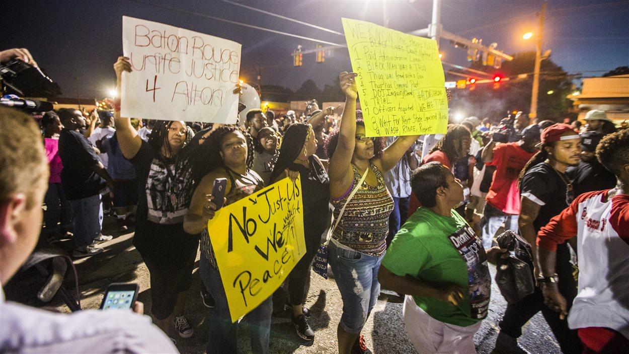 Des manifestants dans les rues de Baton Rouge tiennent des pancartes où il écrit : Justice pour Alton Sterling.