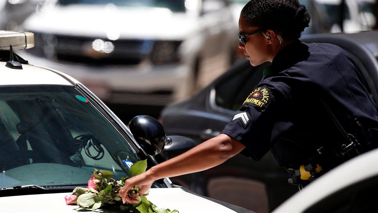 Une policière de Dallas ramasse un bouquet de fleurs sur sa voiture après une veillée de prières dans un parc.