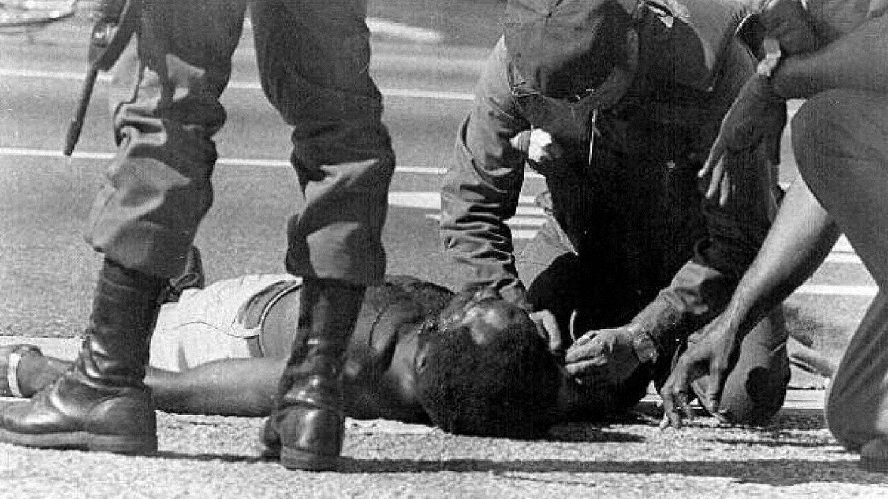 Une victime des émeutes de Liberty City de 1980 est soignée en pleine rue.