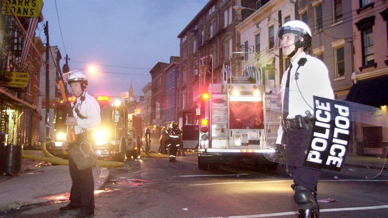 Des policiers de Cincinnati montent la garde le 10 avril 2001 pendant que des pompiers combattent un incendie à la suite des émeutes qui ont secoué la ville.