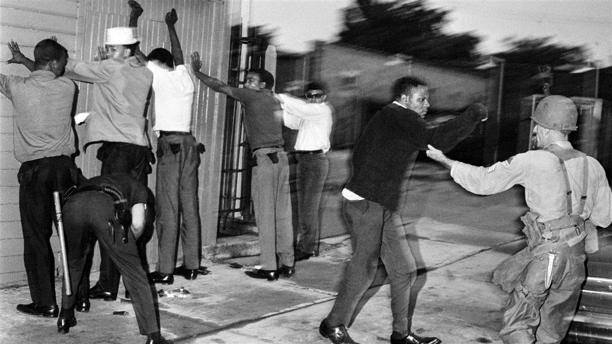 Les forces de l'ordre fouillent des hommes à Newark, au New Jersey, le 15 juillet 1967, au cours des émeutes qui secouent la ville.