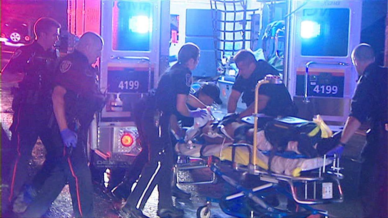 Des ambulanciers et des policiers au secours de la victime