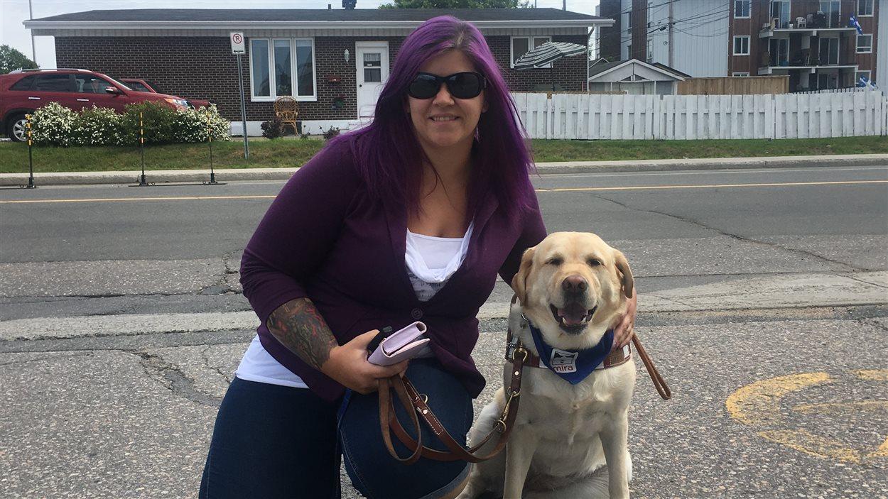 La propriétaire de la nouvelle garderie, Annie Thiebault, pose avec la chienne qui accompagne sa fille autiste.