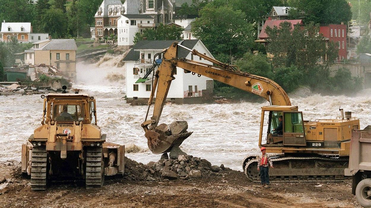 Des grues effectuent du remplissage lors du déluge du Saguenay de 1996.